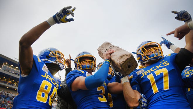 South Dakota State University's Adam Anderson, from left, Taryn Christion and Alex Romenesko hold the Dakota Marker up to the student section after their win over North Dakota State University Saturday, Nov. 4, at Dana Dykhouse Stadium in Brookings.