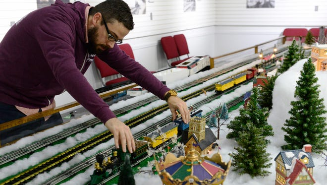 """Kevin Moore, associate curator of artifacts, sets up the """"Hayes Train Special"""" model train display open through Sunday, Jan. 7."""