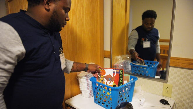 Youth Care Provider Jerrone Holmes shows a box of books that children get when they come to Children's Inn Monday, Nov. 27, in Sioux Falls. Holmes said they will give each child a box of books to read around bedtime for children that stay the night there.