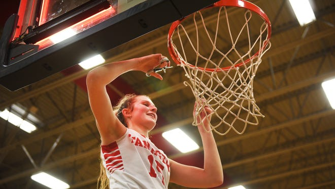 Vermillion's Kasey Herbster cuts the net after their win against Dell Rapids Thursday, March 1, at Tea Area High School in Tea.