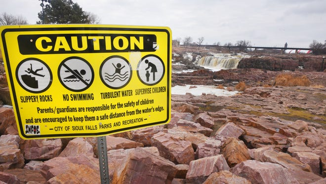 Falls Park caution signs Monday, March 19, in Sioux Falls.