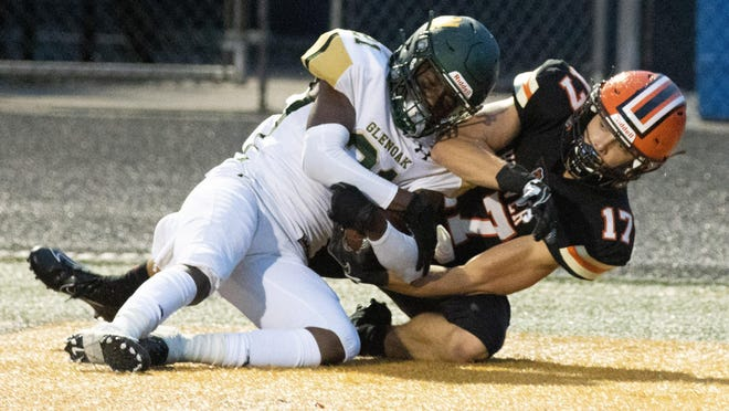 GlenOak's Khimani McNeill (left) and Hoover's Brock Henne fight for possession of the ball during the first quarter, Friday, Aug. 28, 2020.