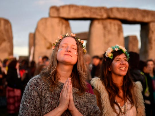 People gather to see the sun rise at the ancient stone