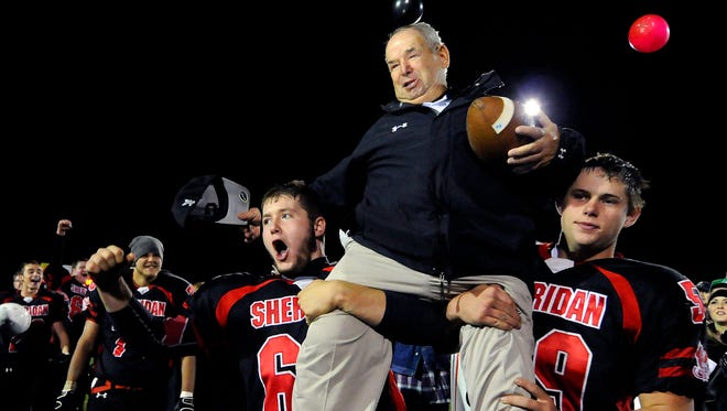 Sheridan High School coach Bud Wright was hoisted by players Nathan Miller, left, and Cole Zeiler, after the team's victory over Lapel High School on Oct. 28, 2011. That game made Wright Indiana's winningest coach with 369 victories. He now has 392 wins spanning 49 years.