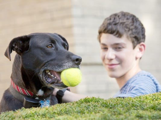 Jacob Rubin, 14, plays with his dog Bailey at his home in Long Grove, Ill.