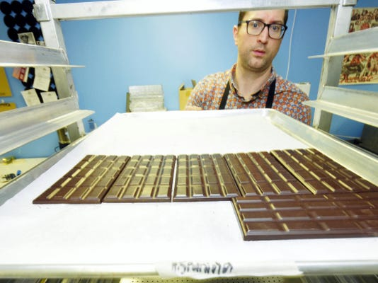 Nathan Miller peeks through a tray of chocolates inside his Chambersburg business on Friday. For the second straight year, Nathan Miller Chocolate is a finalist in the national Good Food Awards, with its popular gingerbread bar.