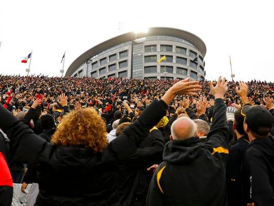 In this Nov. 4, 2017, photo, Iowa fans wave to children