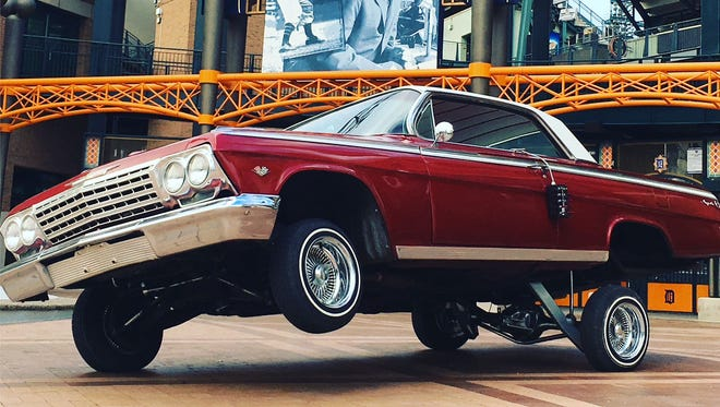 A 1962 Chevrolet Impala 2 door hard top is lifted on 3 wheels outside of Comerica Park in Detroit.
