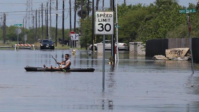 A man kayaks flood waters on Glenoak Drive in Flour Bluff on May 16, 2016.