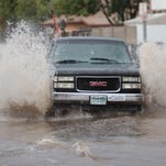 Vehicles attempt to pass through 39th Avenue between Peoria Avenue and Cactus Road on Saturday, September 27, 2014, in Phoenix.
