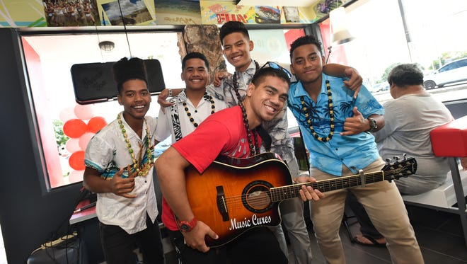 Local band Kids From Chuuk pose for a group photo during the reopening of the KFC restaurant in Dededo on Sept. 17.