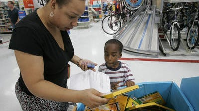With a list of school supplies and calculator in hand, Diamond Emory, left, compares prices of erasable markers with her five-year-old son Eric at a Wal-Mart store  in Canal Winchester, Ohio. Parents trying to tighten the household budget can use shopping for school supplies as an opportunity to teach even young children some important lessons about money.