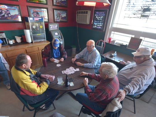 A group of retirees play rummy at Scotty's Saloon in