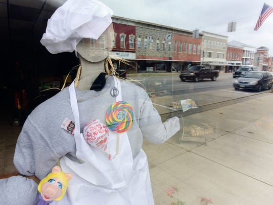 A scarecrow in the front window of Candy Depot on Main Street in Bellevue, decorated for the second annual Scarecrow Contest.