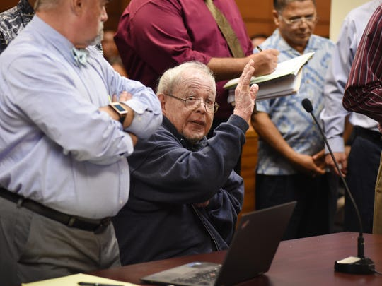 Roland Selvidge, former board member of the Guam Housing and Urban Renewal Authority, raises his hand at his arraignment hearing at the Superior Court of Guam on Aug. 23, 2017.