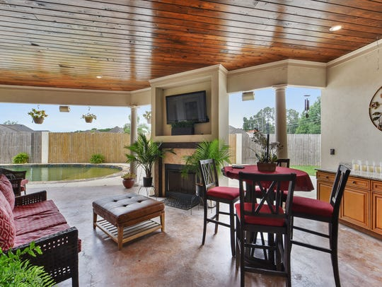 The outdoor kitchen and living   have lovely pool views.