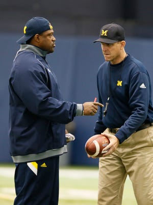 Michigan running backs coach Tyrone Wheatley talks with head coach Jim Harbaugh during football practice on Thursday, March 19, 2015 in Ann Arbor.