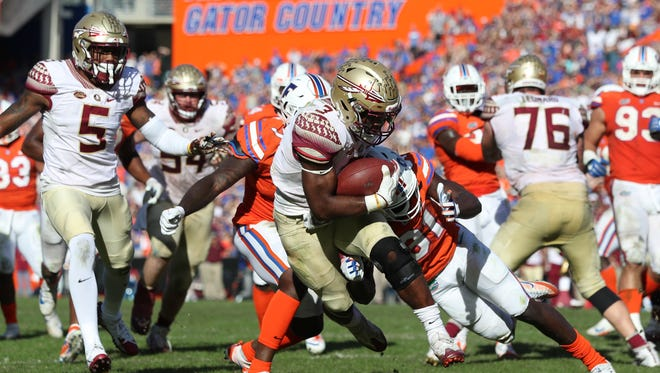 FSU's Cam Akers bounces past Florida's Shawn Davis for a touchdown during the Seminoles 38-22 win at Ben Hill Griffin Stadium in Gainesville on Saturday.
