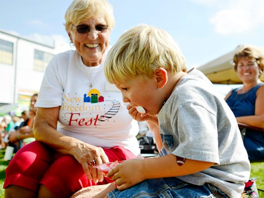Landan Allison, 2, front, eats an icy treat while his Great-Grandmother Lida Thompson, left, and Grandmother Beth Allison, right, all of New Freedom, look on during New Freedom Fest in New Freedom, Pa. on Saturday, Sept. 19, 2015.   Dawn J. Sagert - dsagert@yorkdispatch.com