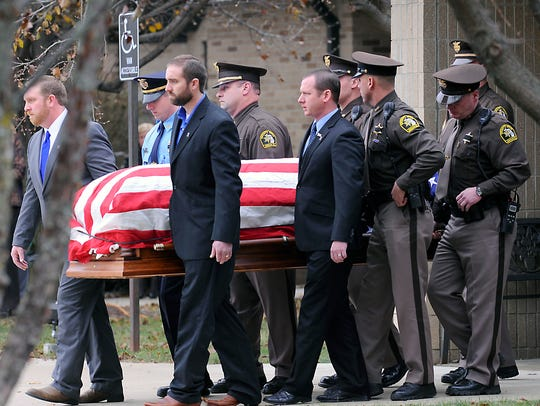 Pallbearers carry out the casket as bout 1500  police