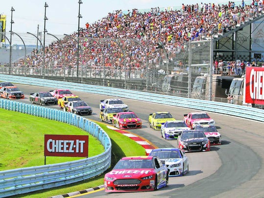 Fans at Watkins Glen International watch a pack NASCAR Sprint Cup Series cars race into Turn 2 during the Cheez-It 355 at The Glen in August. WGI announced it reached a five-year agreement with NASCAR to continue the series through 2020.