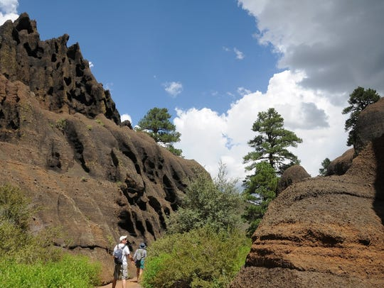 Hikers meander among the hoodoos on the Red Mountain