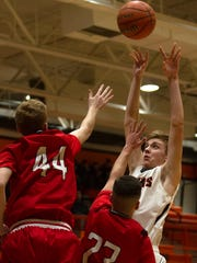 Aztec's Tanner Brooks attempts a shot while defended by Montrose's Kyle Stevenson (44) and  Andru Aragon (23) on Friday at Lillywhite Gym in Aztec.