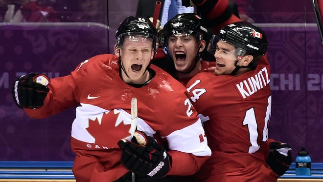 Canada players Corey Perry, left, Matt Duchene, center, and Chris Kunitz, right celebrate on the bench.