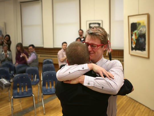 JAC Stringer, founder and director of programming and activism at Heartland Trans Wellness Group, hugs Jason Hettesheimer, 19.