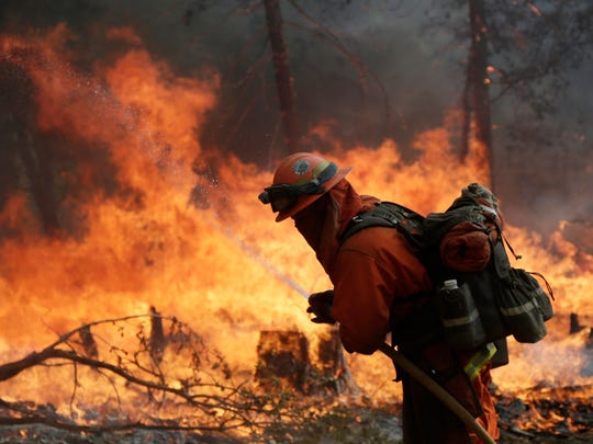 A firefighter with the Gabilan Camp crew hoses down hot spots during a controlled burn to fight the King Fire on Sept. 22, 2014 near Placerville, Calif.
