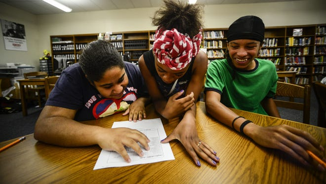 From left, Serena Brown, 16, Ashley Williams, 16, and Lonnie Brown, 15, all from Binghamton, look up an answer during a game as training for their job placement at Broome/Tioga BOCES Summer Youth Employment Program.  KRISTOPHER RADDER / Staff Photo From left to right Serena Brown, 16, Ashley Williams, 16, and Lonnie Brown, 15, all from Binghamton, look up an answer during a Jeopardy game as training for their job placement at Broome/Tioga BOCES Summer Youth Employment Program.