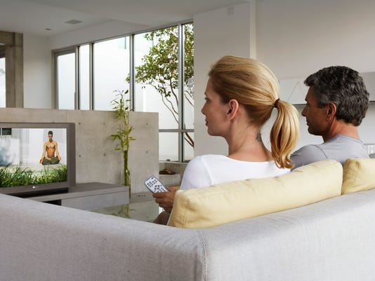 Mature couple on couch watching television, rear view