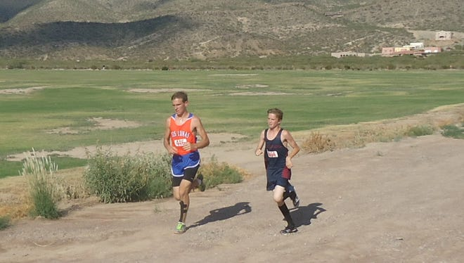 Freshman Wildcat Nick Yacone, right,  is running right with a Las Cruces High runner during the Alamogordo Invitational Cross Country Meet held Friday.