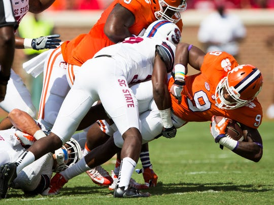 Clemson running back Wayne Gallman (9) runs the ball before getting tackled by SC State defensive back Phillip Henry (36) during the Clemson game against South Carolina State on Saturday, September 17, 2016 in Clemson.