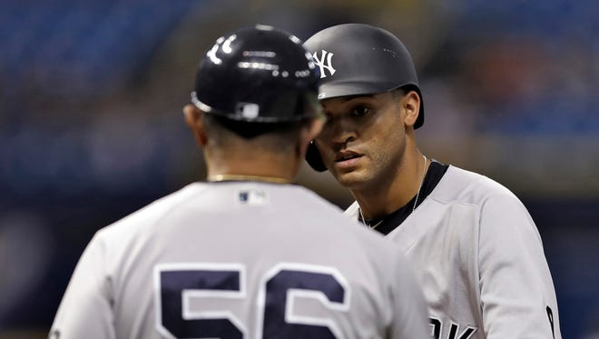 New York Yankees' Mason Williams fist bumps first base coach Tony Pena (56) after his RBI single off Tampa Bay Rays relief pitcher Erasmo Ramirez during the ninth inning of a baseball game Wednesday, Sept. 21, 2016, in St. Petersburg, Fla.