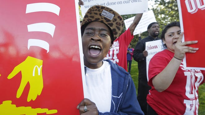 A young man holds a sign as demonstrators gather outside of the McDonald's headquarters Thursday, May 22, 2014, in Oak Brook, Ill., protesting for a $15 an hour wage and the right to unionize. The group gathered outside the entrance as the company held their annual shareholders meeting.