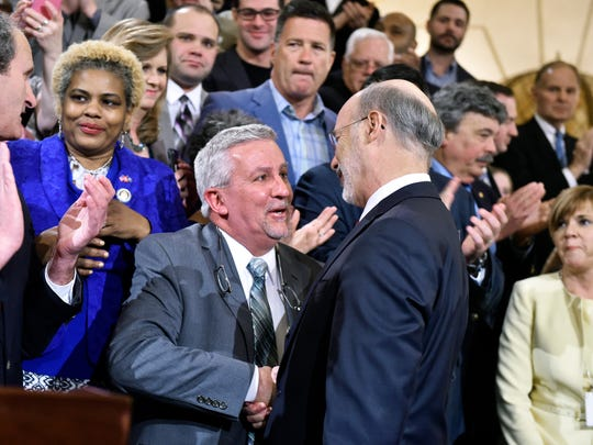 State Sen. Mike Folmer, center, shakes hands with Gov. Tom Wolf in 2016 as advocates celebrated the legalization of marijuana for medical use in Pennsylvania. Folmer was among the driving forces in the General Assembly for passing medical marijuana legislation.