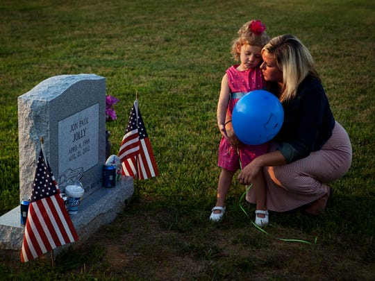 Former heroin addict Katie Warren, right, holds her daughter Ella Jolly, 4, as they visit Ella's father, Jon Paul Jolly's, grave site. They visited the grave to release balloon messages on the one-year-anniversary of his death from a heroin overdose. Aug. 21, 2013