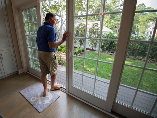 Barry Covington looks out his back porch where he wanted to install a pool at his home in Rehoboth Beach.