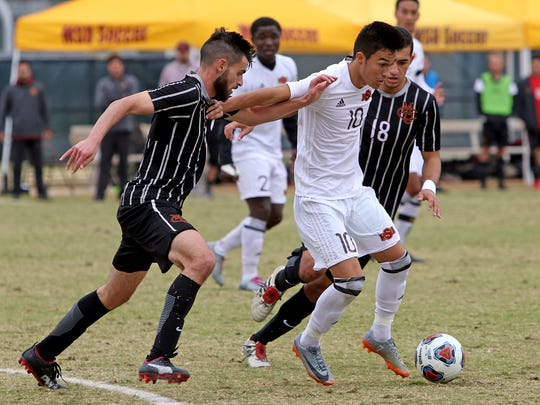 Midwestern State's Sebastian Venegas works to keep Colorado Mesa defenders away before passing Sunday, Nov. 12, 2017, in the NCAA Division II South Central Semifinal at Stang Park. The Mustangs defeated the Mavericks 3-0 to advance.