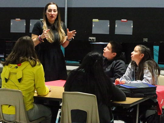 Yvette Garcia, STEAM Academy program coordinator at Camino Real Middle School, on Wednesday offers input to students on how their proposed school app could work.