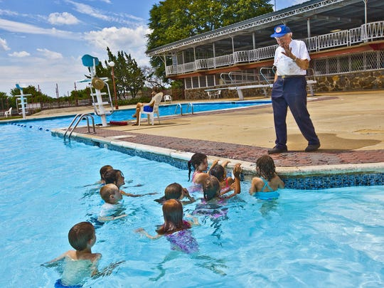 The Rev. Father Balducelli says hi to a group of kids in the pool at St. Anthony in the Hills in 2010.