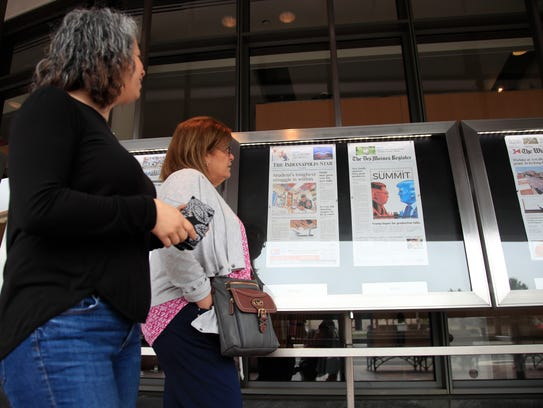 Newseum visitors browse newspaper front pages displayed