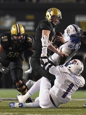 Vanderbilt quarterback Kyle Shurmur (14) is sacked by Tennessee State defensive end Ebenezer Ogundeko (1) in the second half Saturday.