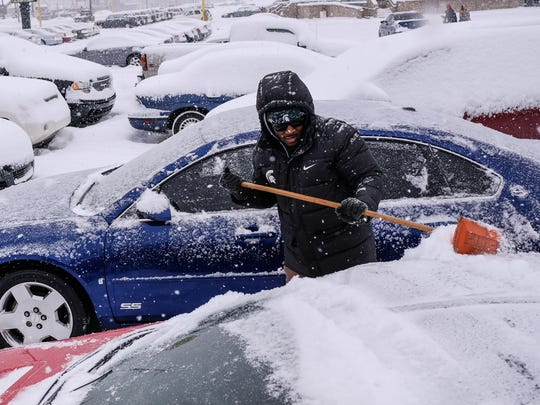 RPM Auto Sales detailer Deandre Johnson clears snow from cars in the lot in Flint for the third time as snow continues to fall on Friday February 9, 2018.