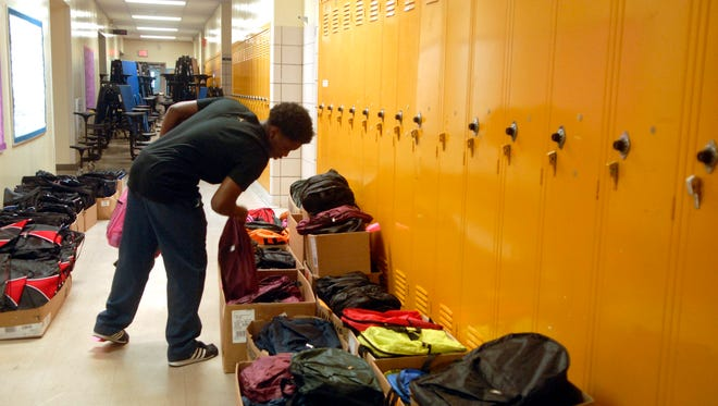 A volunteer organizes backpacks at the 12th Annual Backpack Angel Program, a project of SERVICE FOR PEACE, at Shawnee High School. Aug. 04, 2016
