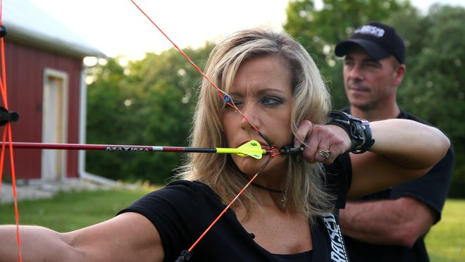 """Karin Holder takes aim with her arrow as her husband, David, stands behind during archery practice on May 27 at their home in rural Winterset. The couple, along with their two children, Warren and Easton, are producing a television show that will premiered on the Outdoor Channel in July, called """"Raised Hunting."""""""