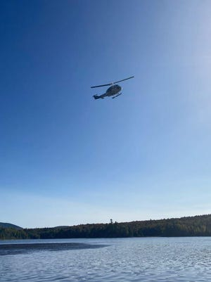 A Maine Forest Service helicopter flies an area around Flagstaff Lake Monday, Sept. 21, 2020, searching for signs of Caitlin Guinta, 31, of York.