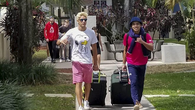 Keiser University student Pol Roch, left and Niklas Nyblom roll their suitcase as they prepare to depart Keiser University Thursday in West Palm Beach. Nyblom is returning to Sweden, while Roch, from Spain is making alternative arrangements for housing.