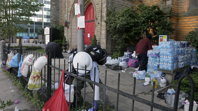 "A ""street medic"" picks up supplies in the yard of Trinity Episcopal Church at East Broad and 3rd streets on Saturday."